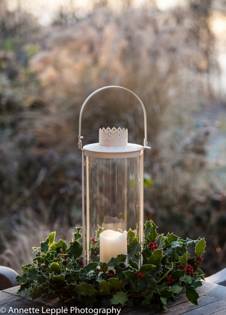 White lantern with candle and holly wreath on garden table in frost