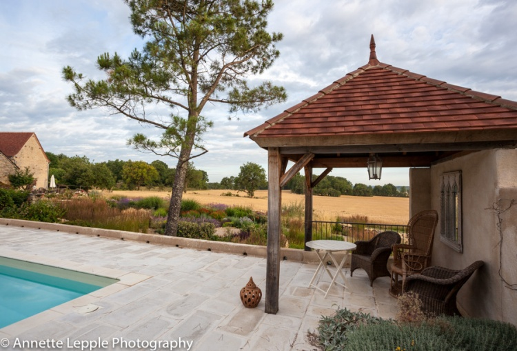 Poolside pavilion with wicker chairs and view onto garden with naturalistic planting and open fields